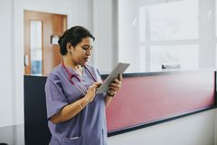 Vrouwelijke verpleegster die het programma controleren op een tablet stock afbeelding