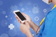 Vrouwelijke verpleegster die het roze mobiele donkere scherm over abstracte blauwe wi met behulp van Stock Foto