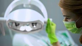 Vrouwelijke verpleegster het aanpassen lichten vóór verrichting, plastische chirurgie, de kosmetiek royalty-vrije stock afbeelding