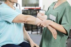 Vrouwelijke Verpleegster Putting Crepe Bandage op de Hand van de Hogere Patiënt Stock Afbeeldingen