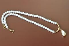 Vrouwelijke versiering: parels op een bruine achtergrond royalty-vrije stock foto's