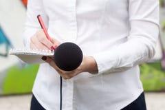 Vrouwelijke verslaggever of journalist bij persconferentie, het schrijven nota's stock fotografie