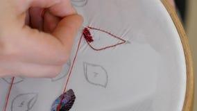Vrouwelijke vingers embroideres een beeld van de kralenversiering royalty-vrije stock afbeeldingen