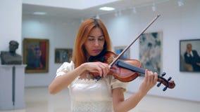 Vrouwelijke violistspelen in een museumruimte met schilderijen op muren stock videobeelden