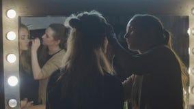 Vrouwelijke visagist die maniermake-up op de voorspiegel van het vrouwengezicht in schoonheidssalon doen stock video