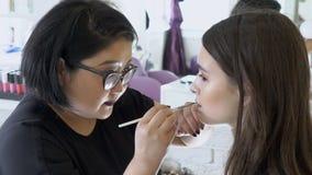 Vrouwelijke visagist schildert lippen van model in schoonheidssalon stock video