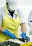 Vrouwelijke vissensnijder op het werk Stock Fotografie