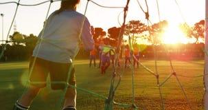 Vrouwelijke voetballer die de bal in doel 4k tegenhouden stock video