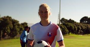 Vrouwelijke voetballer die de bal houdt terwijl teammates zich op voetbalgebied bevinden 4K stock videobeelden