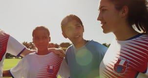Vrouwelijke voetballer die haar team aanmoedigen terwijl het status van wapen om op voetbalgebied te bewapenen 4K stock footage