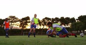 Vrouwelijke voetballer die onderaan een andere speler op voetbalgebied aanpakken 4K stock footage