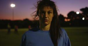 Vrouwelijke voetballer die terwijl het houden van bal op voetbalgebied glimlachen 4K stock videobeelden