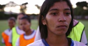 Vrouwelijke voetballer die zich voor haar divers vrouwelijk voetbalteam bevinden op gebied 4K stock videobeelden