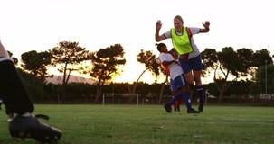 Vrouwelijke voetballer worden die die neer door de concurrentie wordt aangepakt 4K stock videobeelden