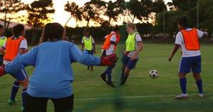 Vrouwelijke voetballers die de bal overgaan terwijl de vrouwelijke speler neer valt 4K stock video