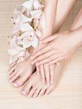 Vrouwelijke voeten bij kuuroordsalon op pedicure en manicureprocedure Stock Fotografie