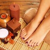 Vrouwelijke voeten bij kuuroordsalon op pedicureprocedure Stock Fotografie