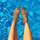 Vrouwelijke voeten in blauw water stock foto's