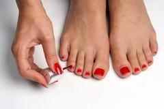 Vrouwelijke voeten die rode spijkers oppoetsen stock foto's