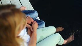 Vrouwelijke voeten die water in de vijver bespatten stock videobeelden