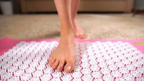Vrouwelijke voeten die zacht op de mat van de acupunctuurmassage worden betreden stock video