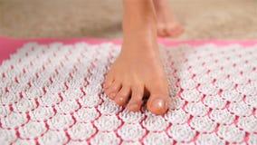 Vrouwelijke voeten die zacht op de mat van de acupunctuurmassage worden betreden Dolly schot stock footage