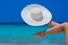 Vrouwelijke voeten en witte hoed op het strand royalty-vrije stock afbeelding