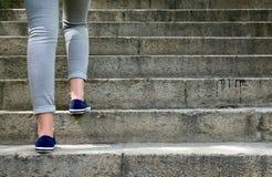 Vrouwelijke voeten in gymschoenen om de treden te beklimmen Stock Foto's