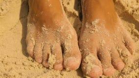 Vrouwelijke voeten in het gele overzeese zand stock video