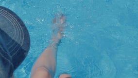 Vrouwelijke voeten in het poolwater stock footage