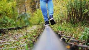 Vrouwelijke voeten onbezorgde gangen langs spoorweg 3840x2160 stock videobeelden