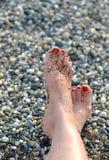 Vrouwelijke voeten op het strand Stock Afbeelding
