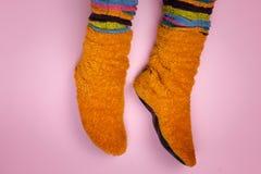 Vrouwelijke voeten in oranje sokken op een roze achtergrond Stock Afbeeldingen
