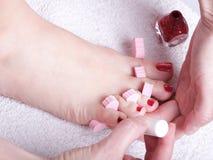 Vrouwelijke voeten rode opgepoetste spijkers Royalty-vrije Stock Foto's