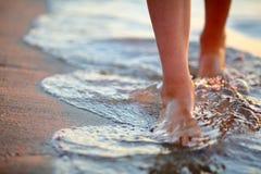 Vrouwelijke voeten stap op de overzeese golf
