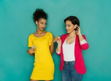 Vrouwelijke vrienden die earbuds bij studioachtergrond delen stock foto's