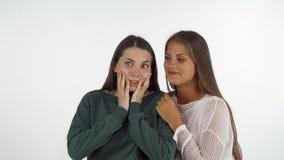 Vrouwelijke vrienden die, het lachen verrast het kijken weg kijken stock video