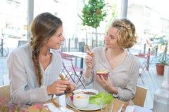 Vrouwelijke vrienden die lunch hebben samen bij restaurant Stock Foto