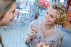 Vrouwelijke vrienden die lunch hebben samen bij wandelgalerijrestaurant Stock Foto