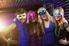 Vrouwelijke vrienden die maskerade in bar dragen stock foto