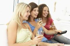 Vrouwelijke Vrienden die op Televisie samen letten royalty-vrije stock afbeeldingen