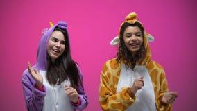 Vrouwelijke vrienden in eenhoorn en girafpyjama's die, Carnaval-partij, prettijd dansen stock video