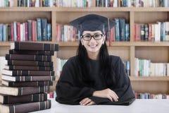 Vrouwelijke vrijgezel en boeken in bibliotheek Stock Foto