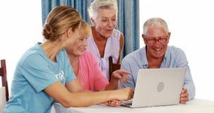 Vrouwelijke vrijwilliger en bejaarden die laptop met behulp van stock videobeelden