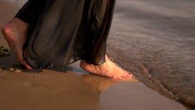 Vrouwelijke vrouwenbenen blootvoets op het zandstrand binnen aan het water stock footage