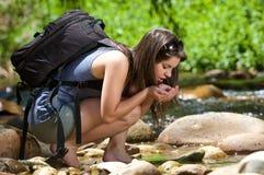 Vrouwelijke wandelaar met rugzak drinkwater van stroom in aard Stock Afbeeldingen