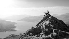 Vrouwelijke wandelaars bovenop de berg die een onderbreking nemen en van een valleimening genieten Royalty-vrije Stock Foto