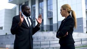 Vrouwelijke werkgever die Afro-Amerikaanse werknemer, mens beledigen die zijn het doen proberen te rechtvaardigen royalty-vrije stock fotografie