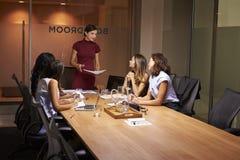Vrouwelijke werkgever en collega's op een avond commerciële vergadering stock fotografie