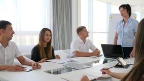 Vrouwelijke werkgever naast laptop holdingsvergadering met Jonge medewerkers in licht bureau stock video